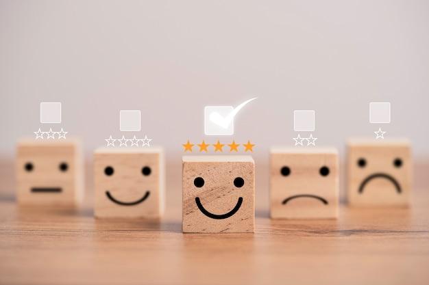 Концепция опроса удовлетворенности клиентов, значки человеческого лица печатают экран на деревянном кубическом блоке со звездами и отметкой для оценки продукта и услуги.