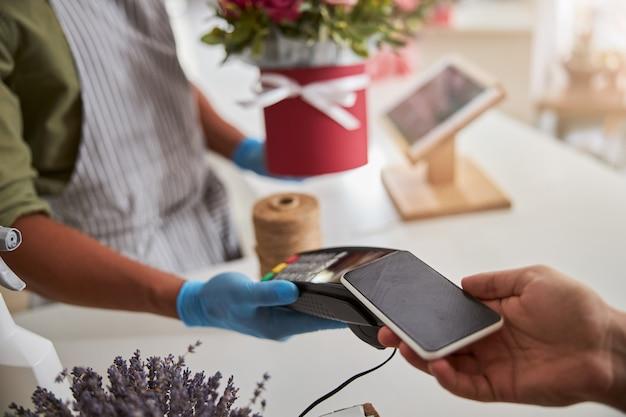매장 매니저의 손에있는 꽃집 결제 단말기에서 스마트 폰을 스캔하는 고객