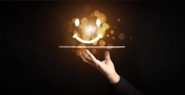 고객 서비스 및 만족 개념, 사업가가 가상 터치 스크린에서 웃는 얼굴 이모티콘을 누릅니다. 서비스에 만족을 주기 위해 행복한 웃는 얼굴 아이콘에. 평가는 매우 인상적입니다.