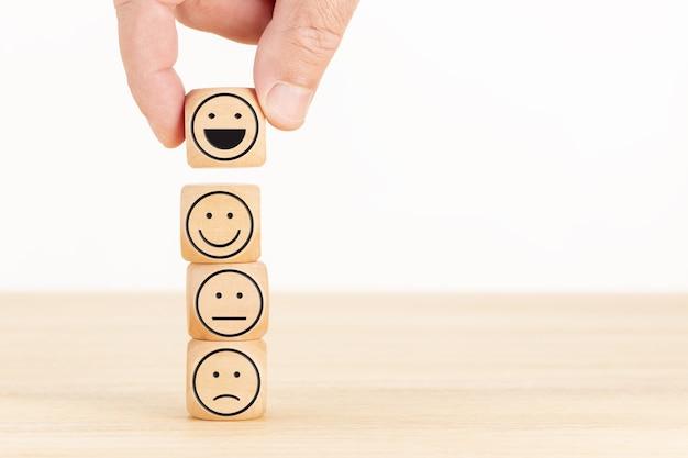 고객 서비스 평가 및 만족도 조사 개념. 손은 나무 블록에 행복한 얼굴 이모티콘을 선택했습니다.