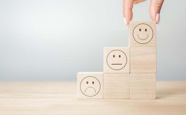 カスタマーサービスの評価と満足度調査の概念。クライアントの手は、木製のブロック、コピースペース、灰色の背景に幸せそうな顔の笑顔の顔のシンボルを選んだ