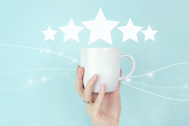 Концепции оценки обслуживания клиентов и исследования удовлетворенности. девушка рукой держать утреннюю кофейную чашку с пятью звездами 5 значок знака рейтинга на синем фоне. обзор, рейтинг, удовлетворенность.