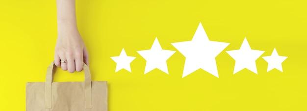 Концепции оценки обслуживания клиентов и исследования удовлетворенности. сумка для покупок из переработанной коричневой бумаги в руке с голограммой пять звезд 5 рейтинг значок на желтом фоне, плоская планировка. концепция летней распродажи.