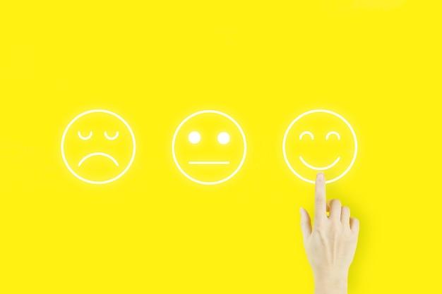 Концепции оценки обслуживания клиентов и исследования удовлетворенности. палец руки молодой женщины указывая с эмоцией лица голограммы на желтом фоне.