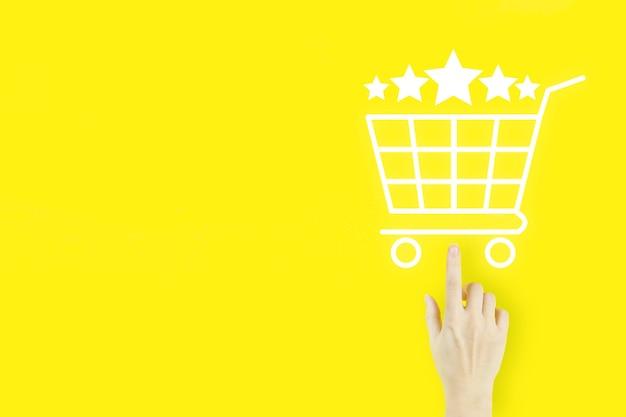 Концепции оценки обслуживания клиентов и исследования удовлетворенности. палец руки молодой женщины указывая с голограммой магазинная тележкаа и рейтинг 5 звезд 5 на желтом. обзор, рейтинг, удовлетворенность.