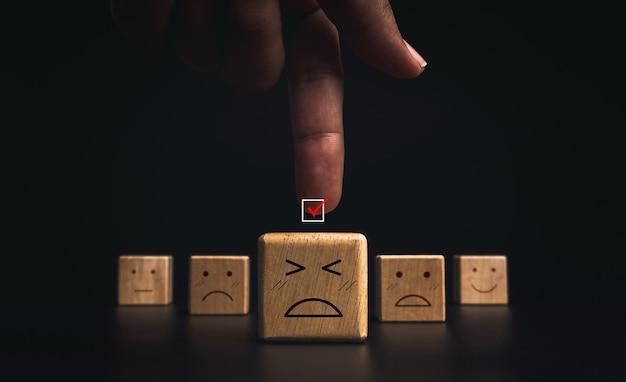 カスタマーサービスの評価、悪い評価、フィードバック、および満足度調査の概念。暗い背景の木製ブロックに悲しくて失敗した絵文字の顔でチェックボックスに赤いチェックマークを指している手。