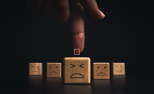 Customer service evaluation, bad rating, feedback, and satisfaction survey concept. hand pointing red checkmark on the checkbox with sad and failed emoticon face on wooden block on dark background.