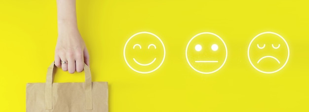Customer service evaluation concept. recycled brown paper shopping bag in hand with hologram face emotion icon on yellow background, flat lay. summer sale concept. delivery service concept.