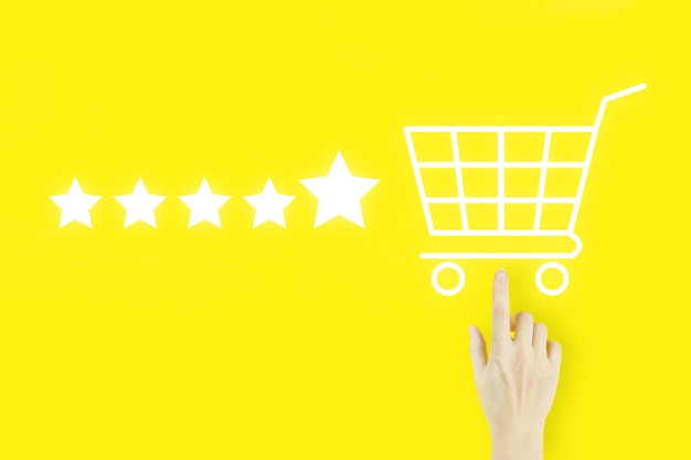 Customer service evaluation concept. young woman's hand finger pointing with hologram shopping cart and five stars 5 rating on yellow background. increase rating evaluation and classification concept.