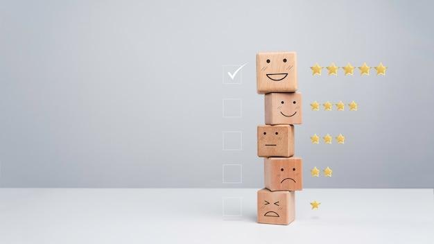 고객 서비스 평가, 피드백 및 만족도 조사 개념. 흰색, 복사 공간에 다른 감정 얼굴에 쌓인 행복한 웃는 이모티콘 나무 큐브 블록의 확인란에 확인 표시를 합니다.