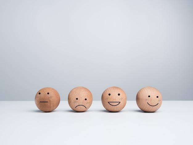 고객 서비스 평가, 피드백 및 만족도 조사 개념. 복사 공간이 있는 흰색 배경에 다른 감정적인 얼굴이 있는 귀여운 행복한 웃는 이모티콘이 있는 나무 공.