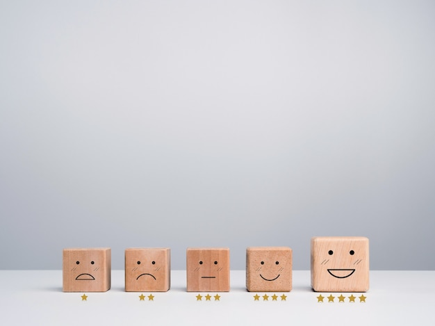 Customer service evaluation, feedback, and satisfaction survey concept. wooden cube blocks with a cute smiley emoticon with emotion faces and rating gold stars on white background with copy space.