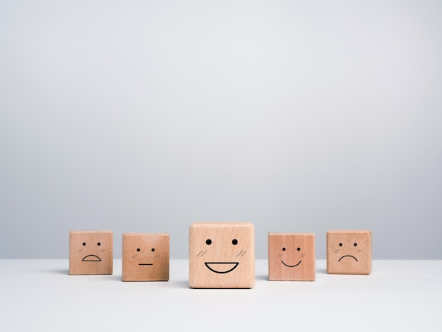Customer service evaluation, feedback, and satisfaction survey concept. wooden cube blocks with a cute smiley emoticon with emotion faces on white background with copy space.