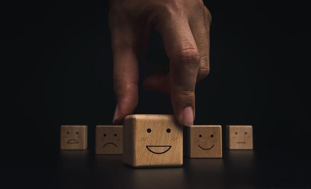 고객 서비스 평가, 평가, 피드백 및 만족도 조사 개념. 어두운 배경의 나무 블록에 있는 행복한 미소 이모티콘 얼굴을 손으로 따기.