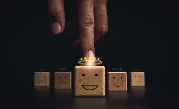 고객 서비스 평가, 평가, 피드백 및 만족도 조사 개념. 어두운 배경에 있는 나무 블록에 5개의 황금 별이 있는 행복한 미소 이모티콘 얼굴을 가리키는 손.