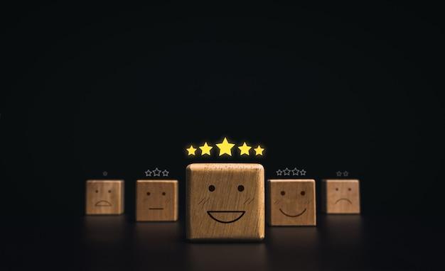 고객 서비스 평가, 평가, 피드백 및 만족도 조사 개념. 어두운 배경에 있는 나무 블록에 5개의 황금 별이 있는 행복한 미소 이모티콘 얼굴.
