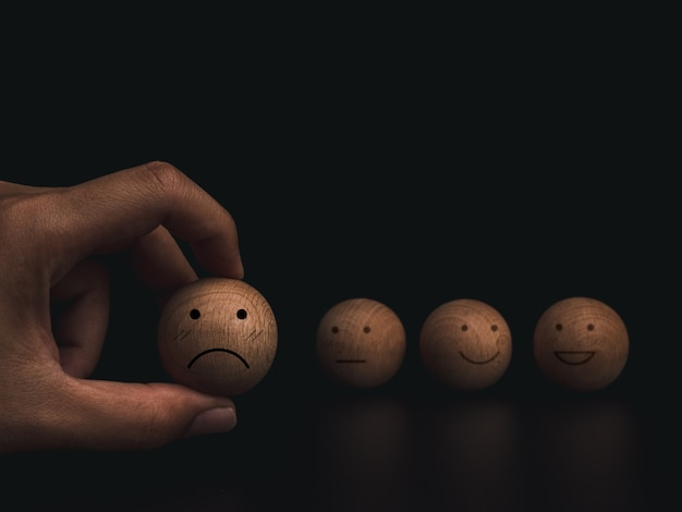 Customer service evaluation, rating, feedback, and satisfaction survey concept. hand holding sad and failed emoticon face on wooden ball on dark background.