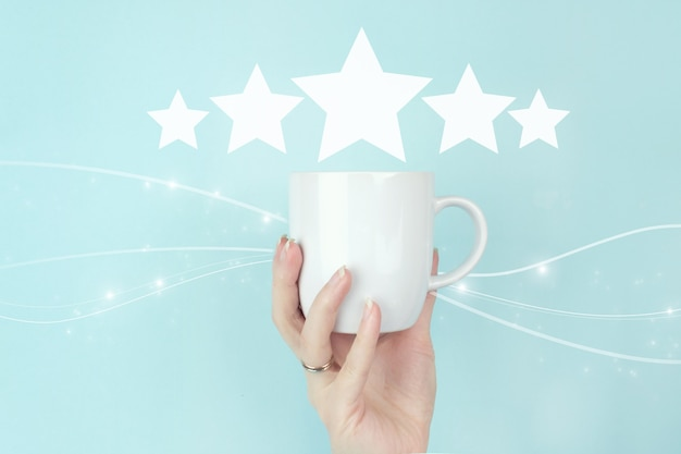 Customer service evaluation and satisfaction survey concepts. girl hand hold morning coffee cup with five stars 5 rating sign icon on blue background. review, rating,satisfaction.