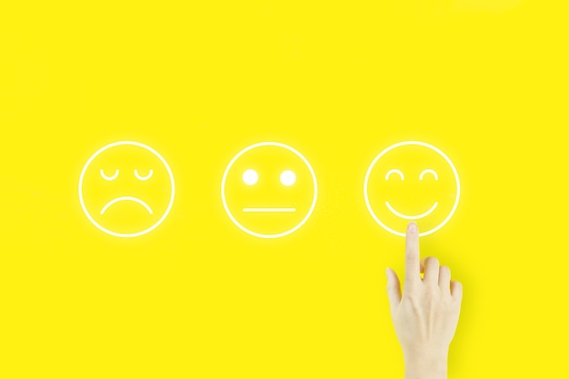 Customer service evaluation and satisfaction survey concepts. young woman's hand finger pointing with hologram face emotion on yellow background.