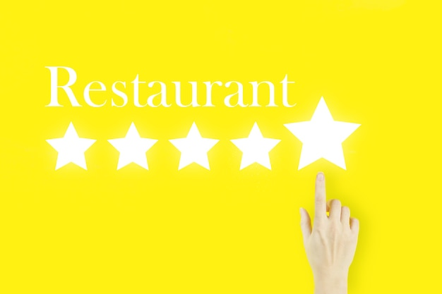 Customer service evaluation and satisfaction survey concepts. young woman's hand finger pointing with hologram five stars and text restaurant on yellow background. review, rating,satisfaction.