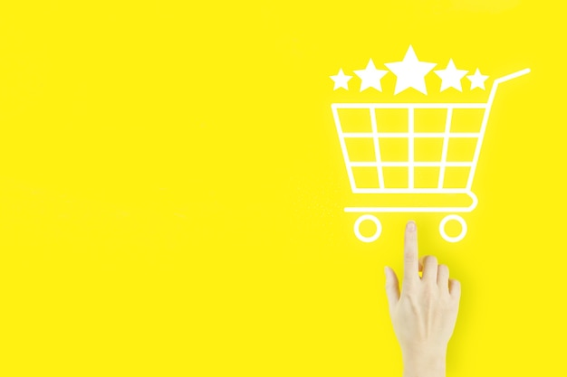 Customer service evaluation and satisfaction survey concepts. young woman's hand finger pointing with hologram shopping cart and five stars 5 rating on yellow. review, rating,satisfaction.