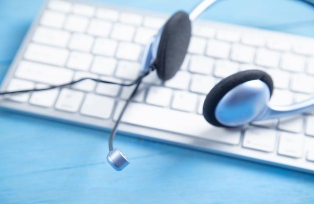 Гарнитура обслуживания клиентов и клавиатура компьютера на синем фоне.