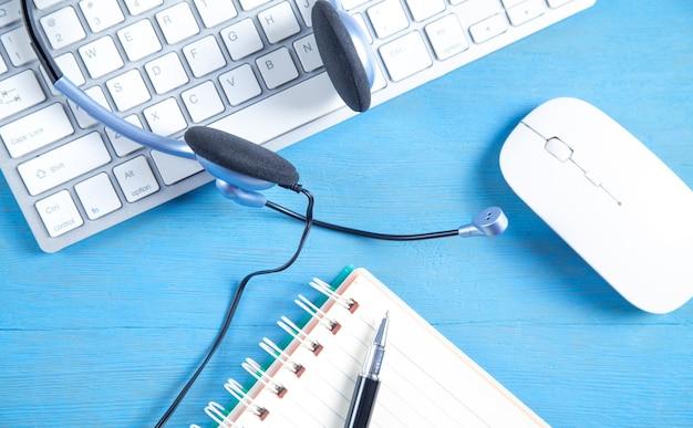 Гарнитура обслуживания клиентов, клавиатура компьютера и бизнес-объекты на синем фоне.