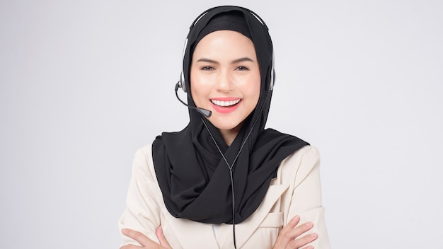 Customer service operator muslim woman in suit wearing headset over white background studio