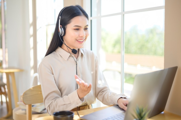 A customer service operator woman in headset using computer answering customer call in office