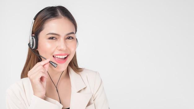 Оператор обслуживания клиентов женщина в костюме носить гарнитуру на белом фоне студии