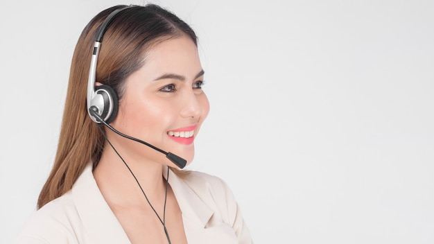 Customer service operator woman in suit wearing headset over white background studio