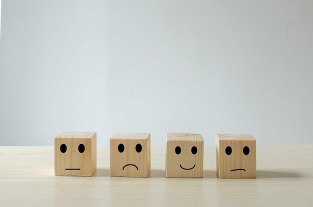 Рейтинги обслуживания клиентов и концепция эмоций обратной связи деревянный куб. опрос удовлетворенности с отрицательными, нейтральными и положительными выражениями лица