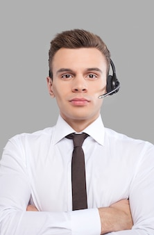 고객 서비스 담당자. 정장을 입은 쾌활한 청년이 헤드셋을 조정하고 회색 배경에 서 있는 동안 카메라를 보며 웃고 있습니다.