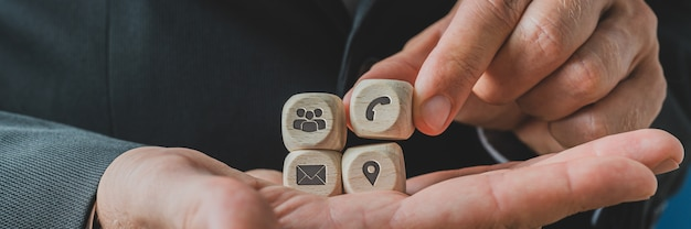 Customer service representative holding wooden dices with contact