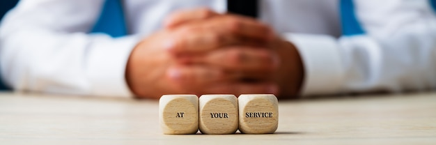 Customer service representative sitting behind wooden dices carrying an at your service sign  wide view image