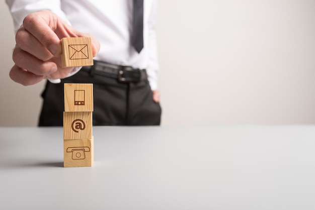 Customer service and support concept - businessman placing wooden blocks with communication icons one on top of the other.