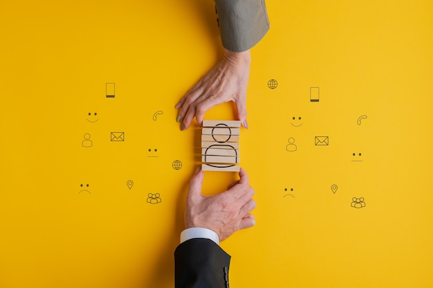 Customer service and support conceptual image - hands of business partners assembling a people icon on wooden blocks.