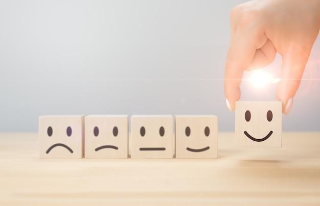 고객 서비스 최고의 비즈니스 평가 경험. 사업가의 손은 미소를 선택합니다. 피드백, 등급, 순위, 서비스 또는 제품에 대한 고객 리뷰를 위한 나무 큐브의 감정 아이콘