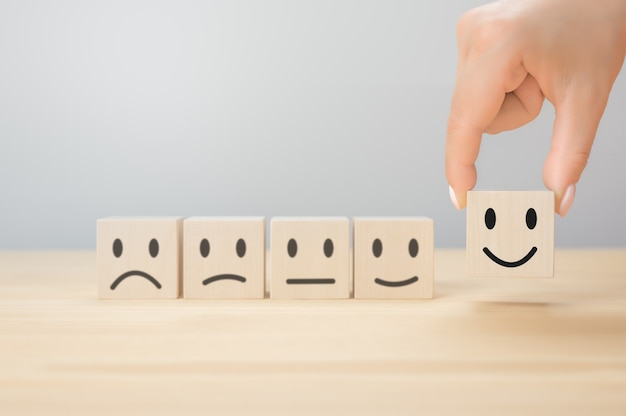 カスタマーサービスは、最高の優れたビジネス評価経験を提供します。満足度調査のコンセプト。ビジネスマンの手は灰色の背景に笑顔の木製の立方体を選択します。コピースペース