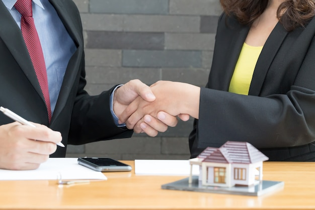 Customer shakes hands and agreement with a real estate agent at the office
