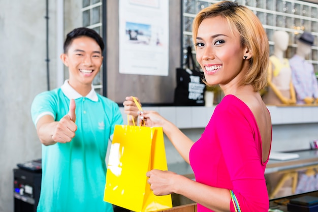 Customer and shop assistant in fashion store