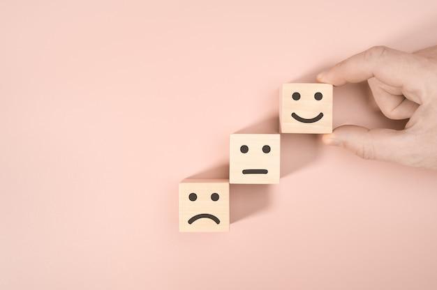ピンクの背景に幸せなアイコンで評価を示す顧客アイコンの顔と積み重ねる木製の立方体ブロック