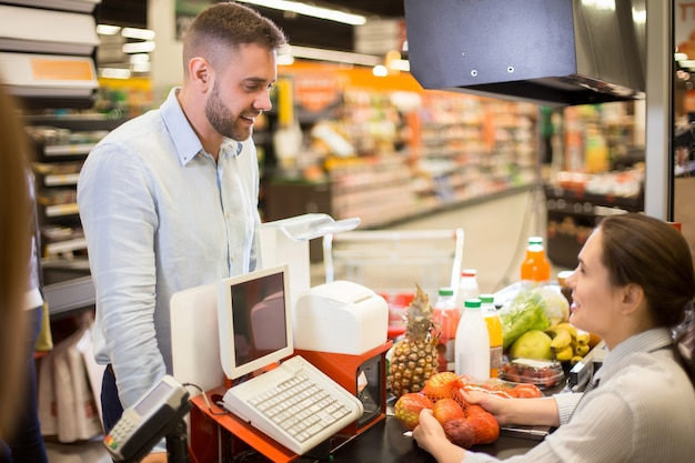 Customer smiling to cashier in supermarket