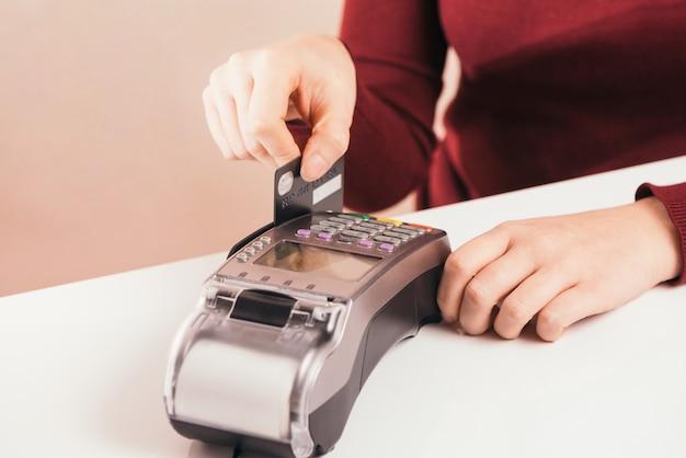 바 카운터 근처의 고객 스탠드는 신용 카드를 사용하여 손 장치보기를 닫고, 현금없는 방법은 상업 공간 개념에서 청구서를 지불합니다.
