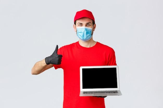 カスタマーサポート、covid-19デリバリーパッケージ、オンライン注文処理コンセプト。赤いユニフォームを着た陽気な宅配便、医療用フェイスマスクと手袋は、ウェブページを推奨し、ノートパソコンの画面と親指を立てます