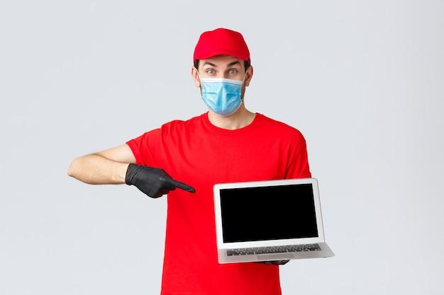 Assistenza clienti, pacchi di consegna covid-19, concetto di elaborazione degli ordini online. corriere entusiasta in uniforme rossa, guanti e maschera facciale da coronavirus, che punta allo schermo del laptop