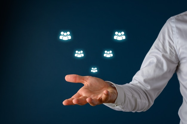 Customer support with male hand under a white glowing people icons floating on visual interface over blue