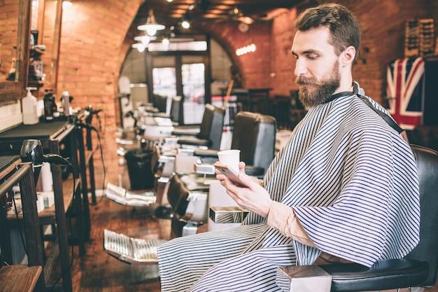 Клиент, который сидит один в кресле. он смотрит на телефон. также мужчина держит чашку чая в правой руке.