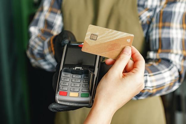 Клиент использует кредитную карту для оплаты в кафе или магазине через терминал с безналичной технологией nfc