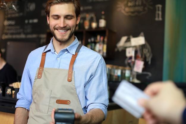 카페 레스토랑, 현금 없는 기술에서 소유자에게 지불하기 위해 신용 카드를 사용하는 고객.